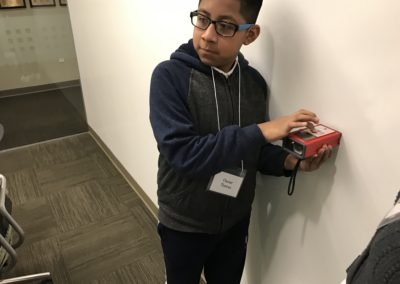 Student uses a digital measuring tool to measure the room